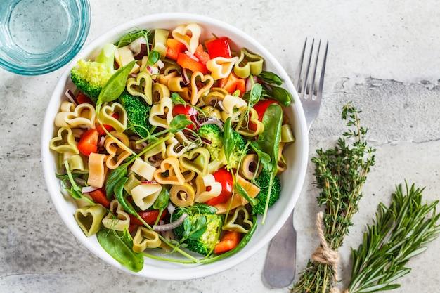 Valentijnsdag concept. salade met pasta harten, olijven, tomaten, spinazie en broccoli in een witte kom.