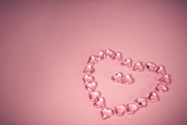 Valentijnsdag concept. twee rode harten in een omgeving glas transparante harten op roze achtergrond, glazen hart gloeit, glas schilderen. veel rode glazen harten. liefde voor valentijnsdag. ruimte kopiëren.