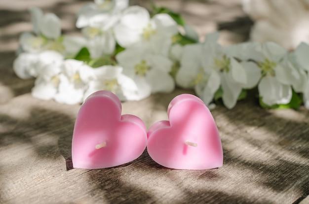 Valentijnsdag concept, twee roze kaarsen in de vorm van harten op een houten tafel met appelboom bloemen met zonnestralen