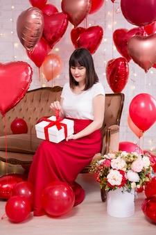Valentijnsdag concept - volledige lengte portret van jonge vrouw zittend op een vintage bank en het openen van de geschenkdoos met rode hartvormige helium ballonnen