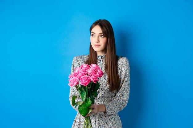 Valentijnsdag concept. vrij romantisch meisje dat dromerig kijkt naar lege ruimte, boeket roze rozen vasthoudt op date, alleen staat op blauwe achtergrond