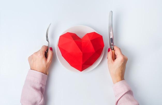 Valentijnsdag concept vrouwelijke handen klaar om papier volume hart te eten op de plaat op een witte achtergrond. bovenaanzicht, plat gelegd.