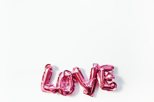 Valentijnsdag creatief concept. opblaasbare roze glanzende folie ballon woordteken liefde met schaduwen geïsoleerd op een witte achtergrond.