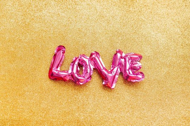 Valentijnsdag creatief concept. opblaasbare roze glanzende folieballon vormige woord love gouden achtergrond.