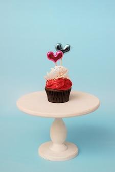 Valentijnsdag cupcake met suiker kant en harten op witte houten standaard