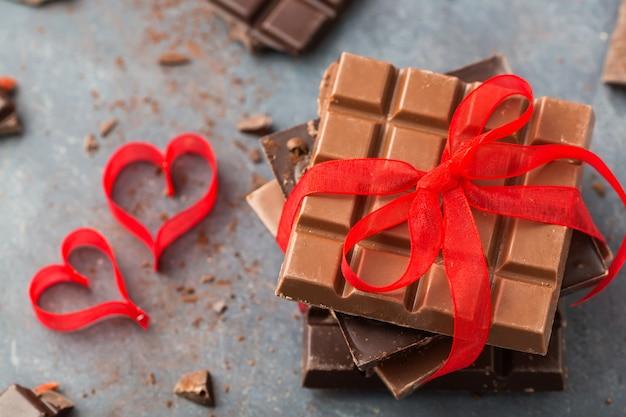 Valentijnsdag. de chocoladerepen verfraaiden rood lint en harten op grijs