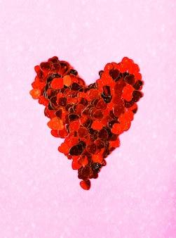Valentijnsdag decoratieve achtergrond met hart gemaakt van klatergoud. sneeuwvaleffect op zachtroze achtergrond.