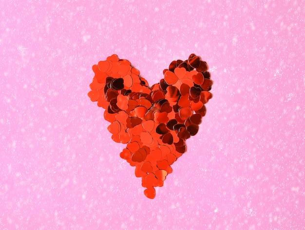 Valentijnsdag decoratieve achtergrond met hart gemaakt van rood klatergoud. sneeuwvaleffect op zachtroze achtergrond.