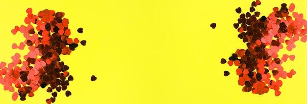 Valentijnsdag decoratieve achtergrond met harten klatergoud. symmetrisch ontwerp. heldere gele banner.