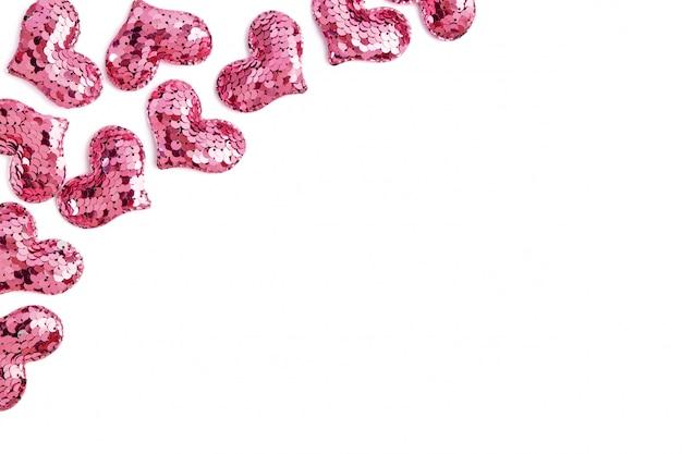 Valentijnsdag decoratieve rand. vele roze lovertjeharten op wit.