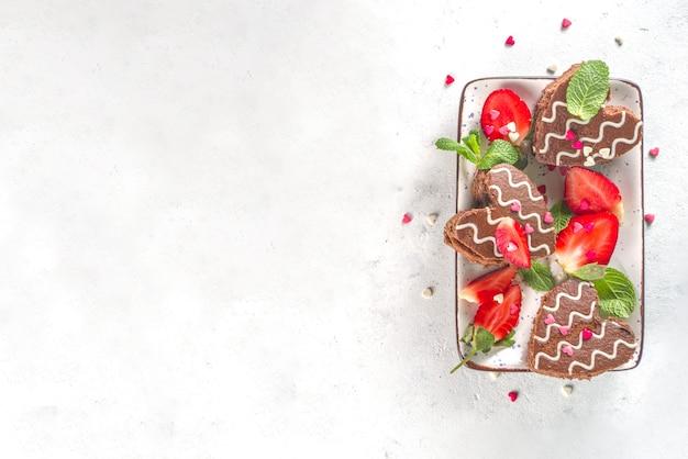 Valentijnsdag dessert. hartvormige chocolade mini cakes met aardbei en munt. bovenaanzicht Premium Foto