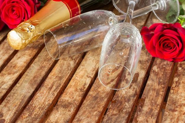 Valentijnsdag donkerrode rozen en paar glazen met hals van champagne wijn