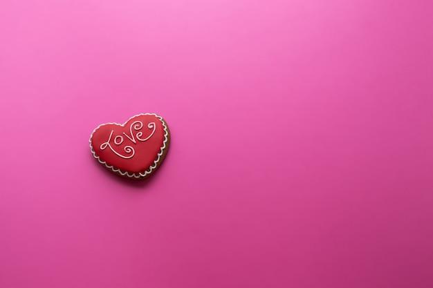 Valentijnsdag, een koekje met een opschriftliefde in de vorm van een hart op een roze,