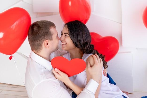 Valentijnsdag, een man met een mooi meisje kijkt elkaar aan met een liefdevolle blik, die een groot rood hart vasthoudt