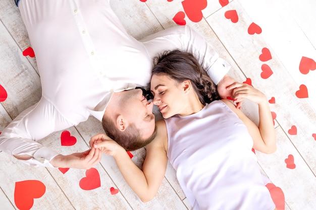 Valentijnsdag, een verliefd paar ligt knuffelend tussen de harten op de grond