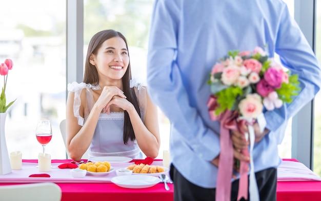 Valentijnsdag en aziatische jonge gelukkige paar concept, close-up van aziatische een man met een boeket rozen vrouw met handen over haar gezicht wacht verrassing na de lunch in een restaurant achtergrond