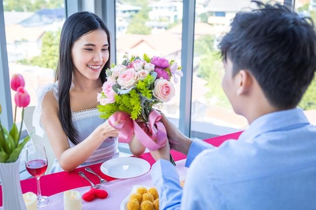 Valentijnsdag en aziatische jonge gelukkige paar concept, een man met een boeket rozen geven aan vrouw met handen glimlachen haar gezicht wacht op verrassing na de lunch in een restaurant achtergrond