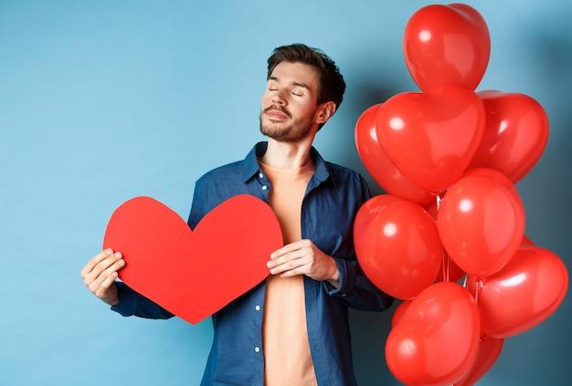 Valentijnsdag en liefde concept. dromerige man met gesloten ogen, romantisch rood hart uitgesneden en staande in de buurt van harten ballonnen, blauwe achtergrond.