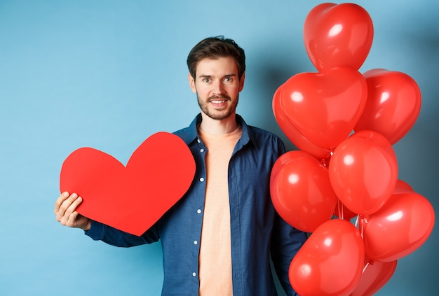 Valentijnsdag en liefde concept. glimlachende jonge man die minnaar met romantische giften, hartballons en valentijnskaartprentbriefkaar wacht, die zich over blauwe achtergrond bevindt.