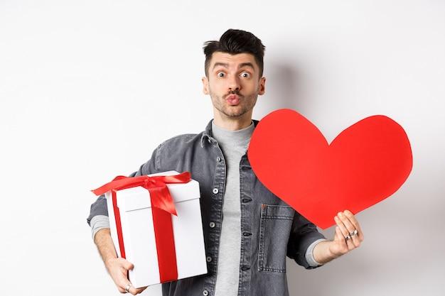 Valentijnsdag en liefde concept. kerel wacht op kus, breng mooie geschenken en rood hart kaart, tuit lippen en kijk naar camera, romantische vakantie vieren.