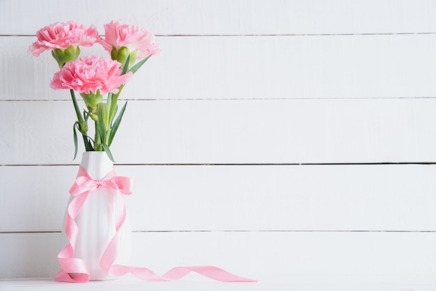 Valentijnsdag en liefde concept. roze anjer in vaas op houten achtergrond.