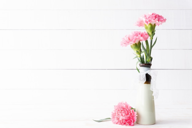 Valentijnsdag en liefde concept. roze anjerbloem in vaas op houten.