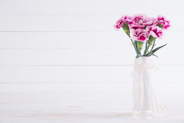 Valentijnsdag en liefde concept. roze anjerbloem in vaas op wit.