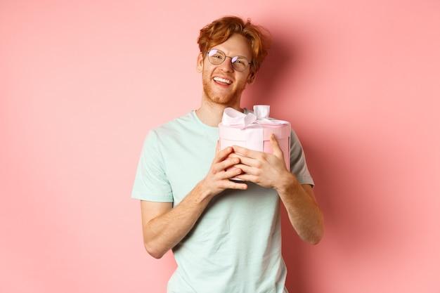 Valentijnsdag en romantiek concept. gelukkig roodharige vriendje ontvangt een romantisch geschenk, knuffelt doos met cadeau en zegt dankjewel, glimlachend dankbaar, roze achtergrond.