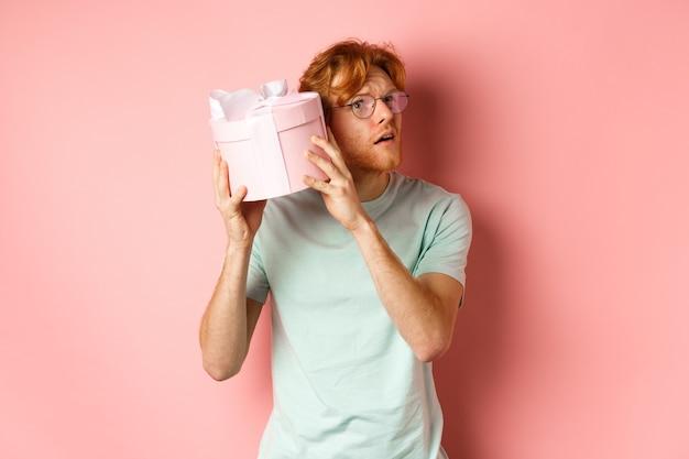 Valentijnsdag en romantiek concept. knappe roodharige man schudt geschenkdoos en vraagt zich af wat erin, probeert te raden aanwezig, staande over roze achtergrond.