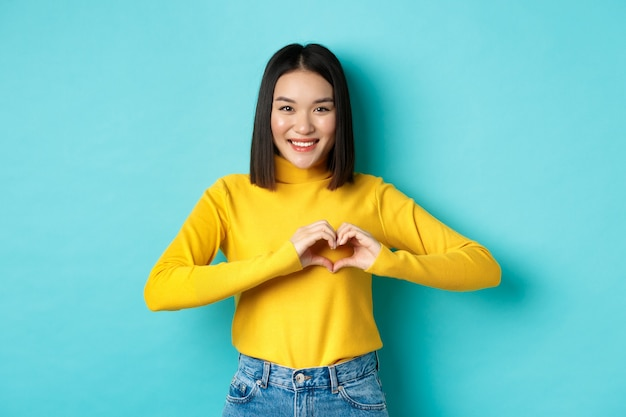 Valentijnsdag en romantiek concept. mooie aziatische vrouw laat zien dat ik van je hou, hartgebaar en glimlachen, staande tegen een blauwe achtergrond