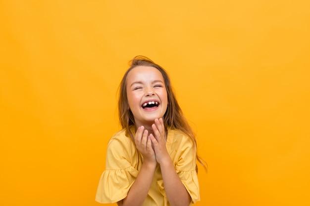 Valentijnsdag en vakantie concept. aantrekkelijk charmant gelukkig meisje kind in een t-shirt en rok glimlacht heel breed en oprecht op een gele achtergrond