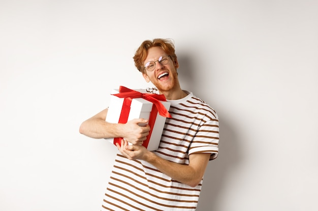 Valentijnsdag en vakantie concept. gelukkig roodharige man knuffelen zijn geschenkdoos en bedanken, kijkend naar camera opgewonden en dankbaar, witte achtergrond.