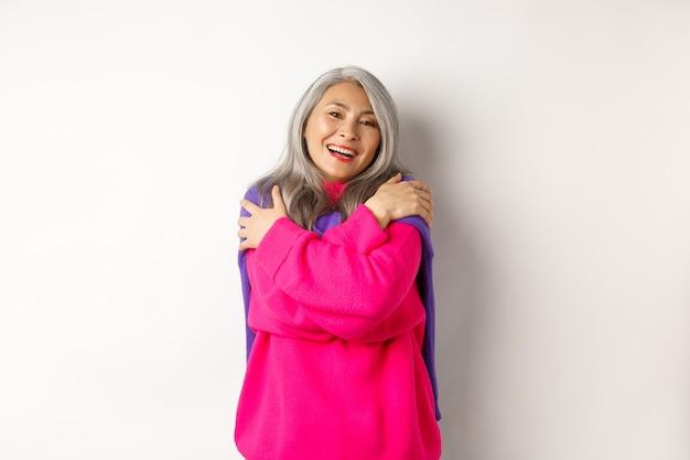 Valentijnsdag en vakantie concept. mooie aziatische senior vrouw in roze trui knuffelen zichzelf met gesloten ogen, glimlachen, staande op een witte achtergrond