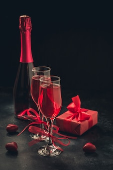 Valentijnsdag en verjaardag wenskaart met cadeau en rode mousserende wijn op zwart.