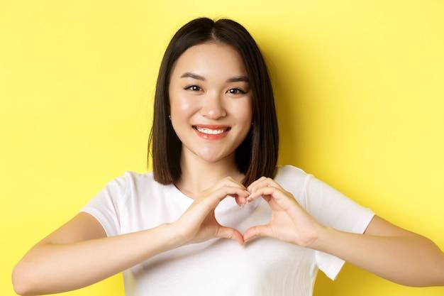 Valentijnsdag en vrouwen concept. close-up van vrij aziatisch meisje in wit t-shirt, glimlachend en hart tonend, ik hou van je gebaar, staande over gele achtergrond.
