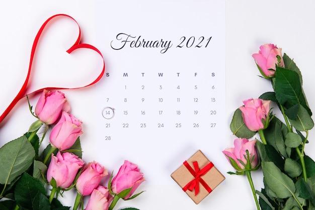Valentijnsdag februari kalender diamanten ring rood hart cadeau en roze rozen op wit