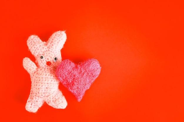 Valentijnsdag feestelijke kaart met gehaakt handgemaakt speelgoedkonijntje en decoratief hart.