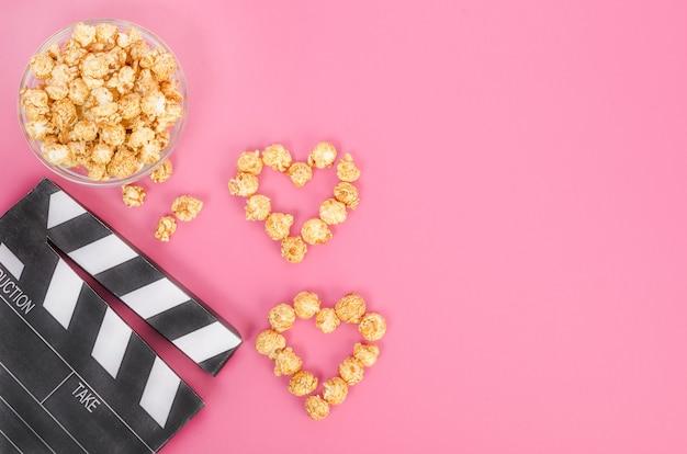 Valentijnsdag film concept. filmklapper met karamel popcorn harten met kopie ruimte op een roze achtergrond.