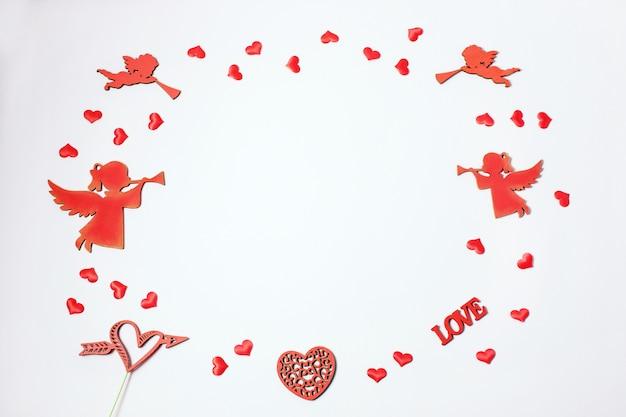 Valentijnsdag. frame gemaakt van geschenken, hart confetti, engelen op roze achtergrond. valentijnsdag achtergrond.