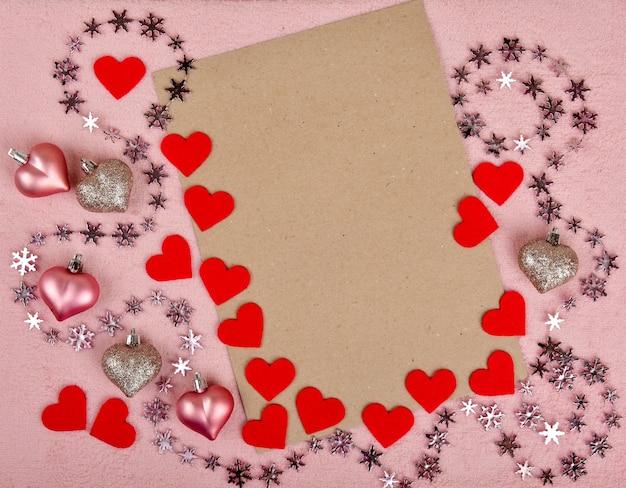 Valentijnsdag frame samenstelling met rode en roze harten, blanco vel papier op pastel roze achtergrond. bovenaanzicht, plat leggen, kopie ruimte.