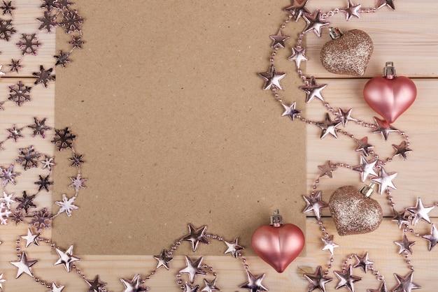 Valentijnsdag frame samenstelling met roze harten, blanco vel papier op houten achtergrond.