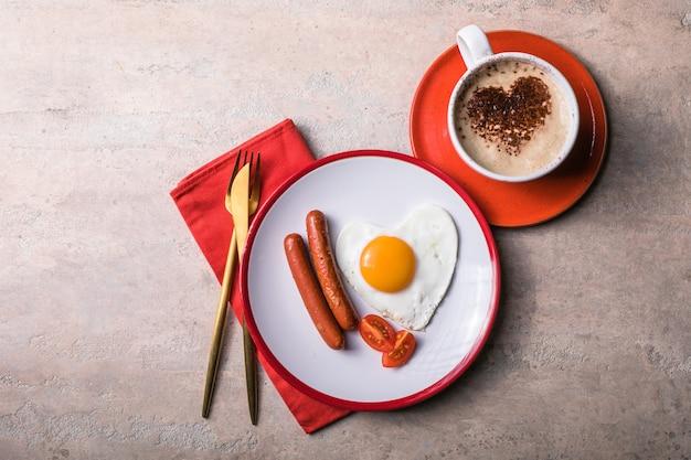 Valentijnsdag gebakken eieren in de vorm van een hart, koffie met vorm