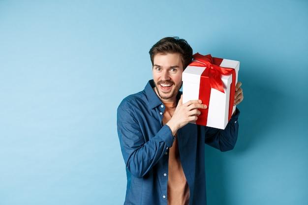 Valentijnsdag. gelukkig jongeman kreeg aanwezig op een speciale feestdag, probeerde te raden wat er in de geschenkdoos zat en glimlachte, staande over de blauwe achtergrond.