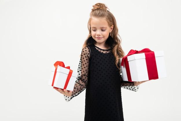 Valentijnsdag . gelukkig kind houdt twee geschenken in handen op een wit