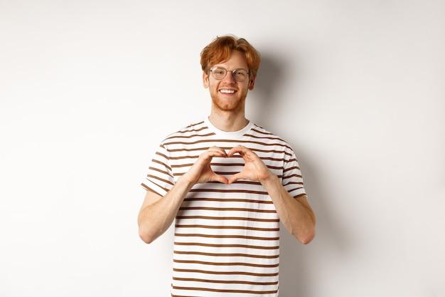 Valentijnsdag. gelukkig vriendje met rood haar, glimlachend en hartgebaar tonen, ik hou van je, staande op witte achtergrond