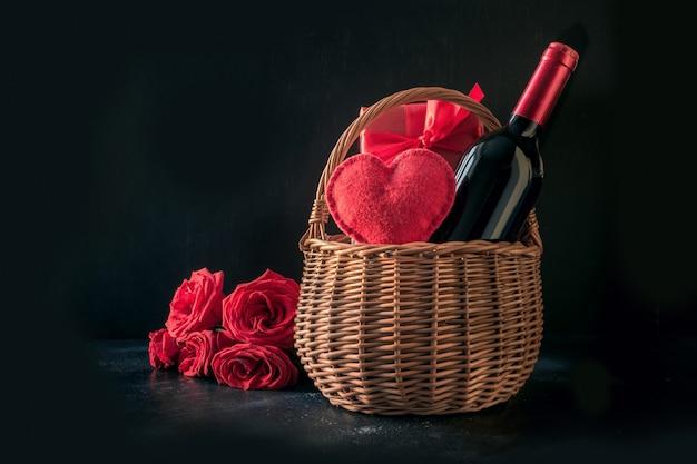 Valentijnsdag geschenk belemmeren, boeket rode rozen, fles mousserende wijn op zwart.