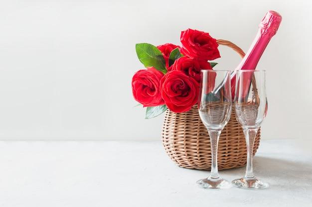Valentijnsdag geschenk belemmeren, boeket van rode rozen, champagne en wijnglazen op wit.