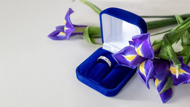 Valentijnsdag geschenk - boeket van blauwe iris bloemen en verlovingsring in blauw fluwelen doos