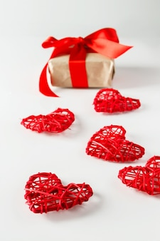 Valentijnsdag geschenk en rode harten op een witte achtergrond. valentijnsdag geschenk op een achtergrond van rode harten van twijgen van twijgen, verticale foto