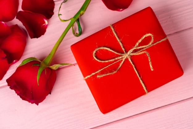 Valentijnsdag geschenk en rose op houten tafel close-up